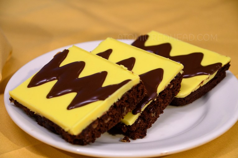 Brownies frosted in yellow frosting with a dark brown zig-zag emulate Charle Brown's t-shirt.
