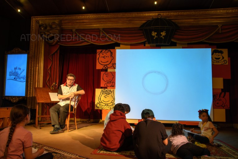 On a stage an artist sits at a desk, behind him a large screen displays what he is drawing on his desk.