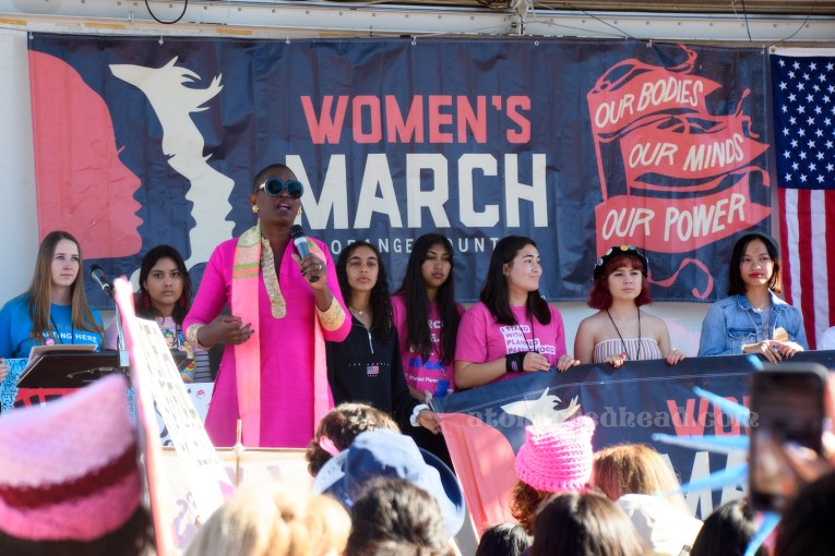 """A speaker takes to the stage, wearing all pink. She is standing in front of a series of young women, many of them also wearing pink. Behind them a large navy banner reads """"Women's March Our Bodies, Our Minds, Our Power"""" and features profiles of women in pink and white."""