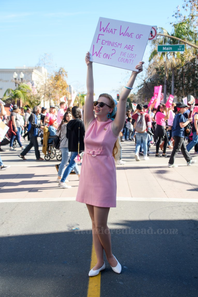 """Myself standing in a pink mini dress holding a sign reading """"What Wave of Feminism Are We On? I've Lost Count"""""""