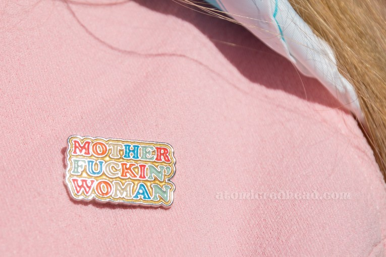 "A small enamel pin featuring multi-colored letters reads ""Motherfuckin' Woman"""