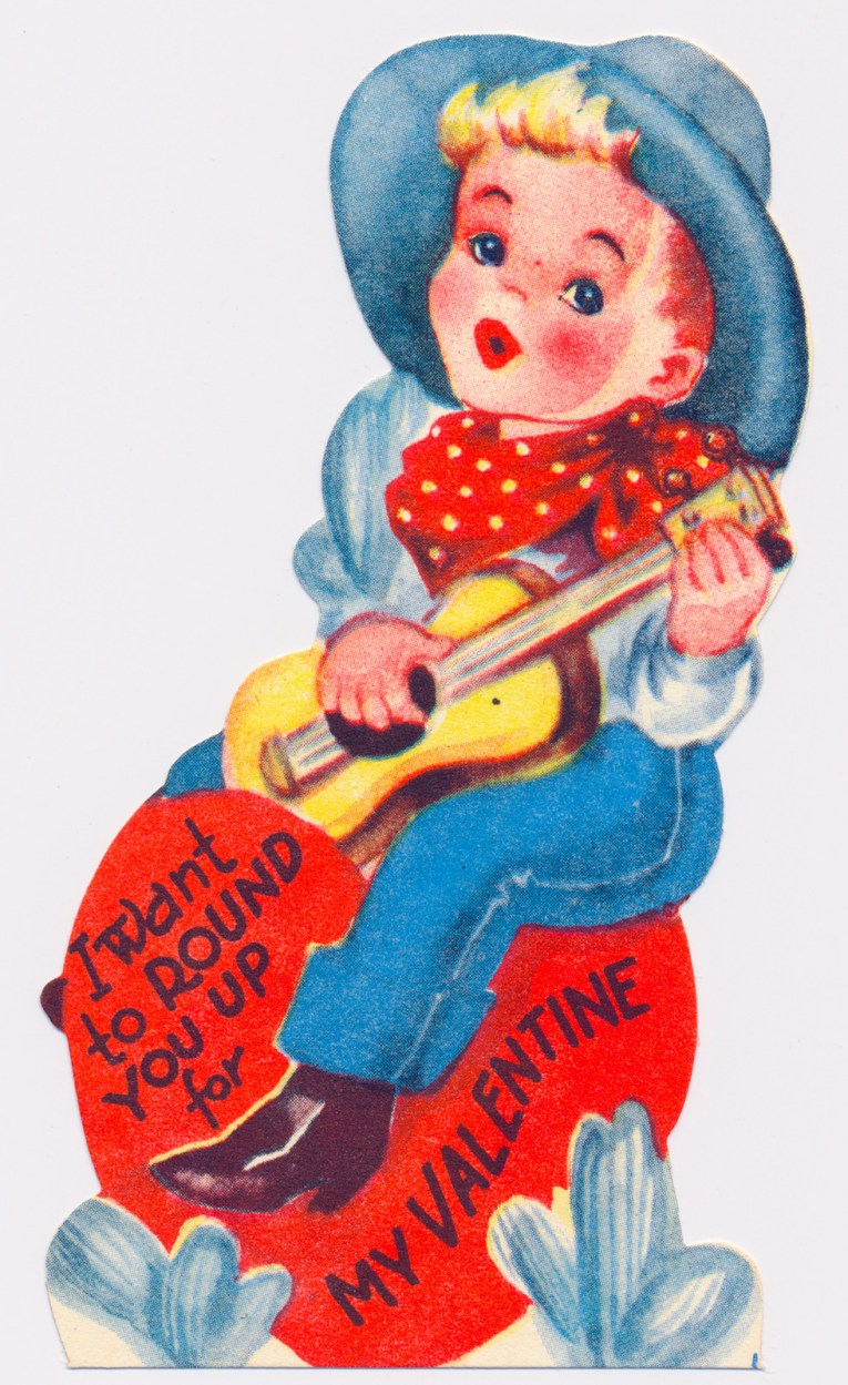 "A cowboy holding a guitar sits on a heart, text reads ""I want to round you up for my valentine"""
