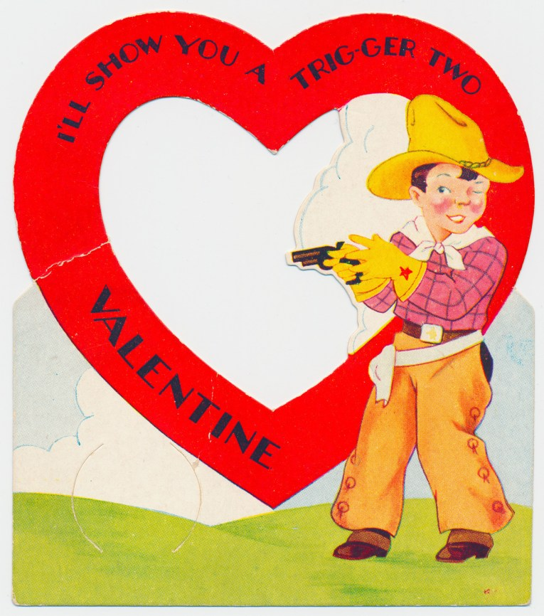 """A cowboy stands near a large heart, text inside the heart reads """"I'll show you a trig-ger two Valentine"""""""