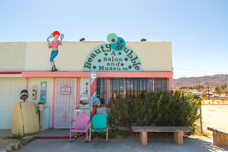 """The outside of the Beauty Bubble, a cream building with orange sherbet trim, a large half circle painted turquoise reads """"The Beauty Bubble Salon and Museum"""" with small bubble like circles rising from it. A cartoon of a woman is painted next to it, who does her hair with hair spray while looking in a mirror. Outside sit a blue and a pink chair, and on the left a sauna hair dryer."""