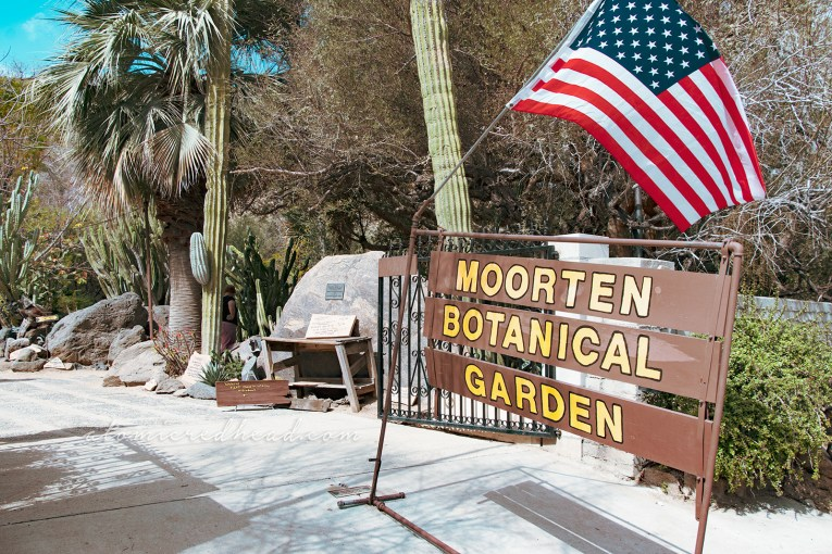 "A brown sign with yellow letters reads ""Moorten Botanical Garden"""
