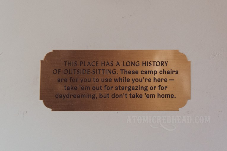 """A small gold plaque reads """"This place has a long history of outside-sitting. These camp chairs are for you to use while you're here - take 'em out for stargazing or day dreaming, but don't take 'em home."""""""