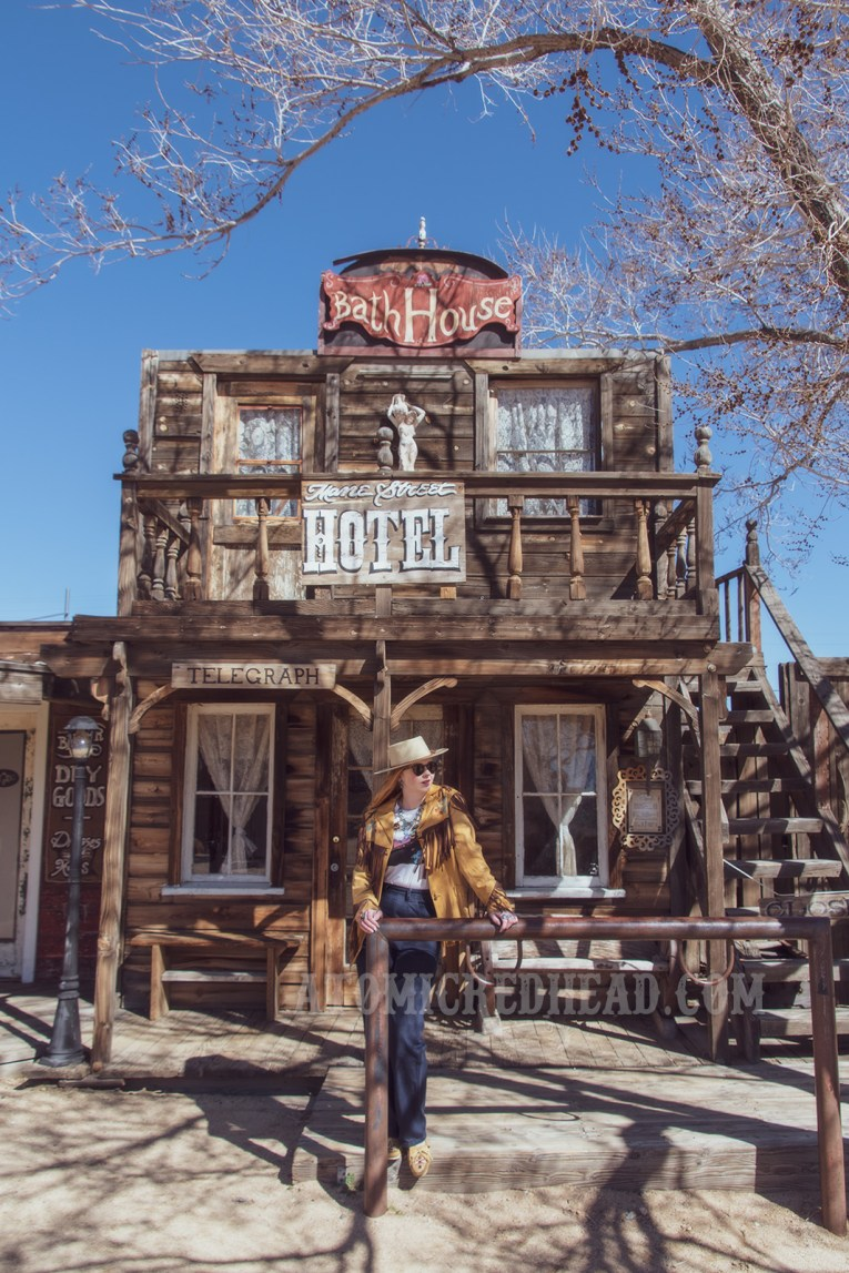 """Myself standing in front of one of the Pioneertown facades, the """"Mane Street Hotel and Bath House"""" wearing a butter yellow leather jacket with dark brown fringe, a t-shirt featuring the cover of the Eagles' album """"Hotel California,"""" jeans, and a cream colored flat top cowboy hat."""
