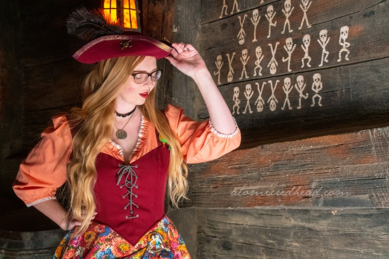Myself, wearing a dress with peach sleeves, maroon corset, and floral skirt, worn over a black skirt to the knee, and a maroon pirate hat, standing in front of small skeletons painted on a wood wall.