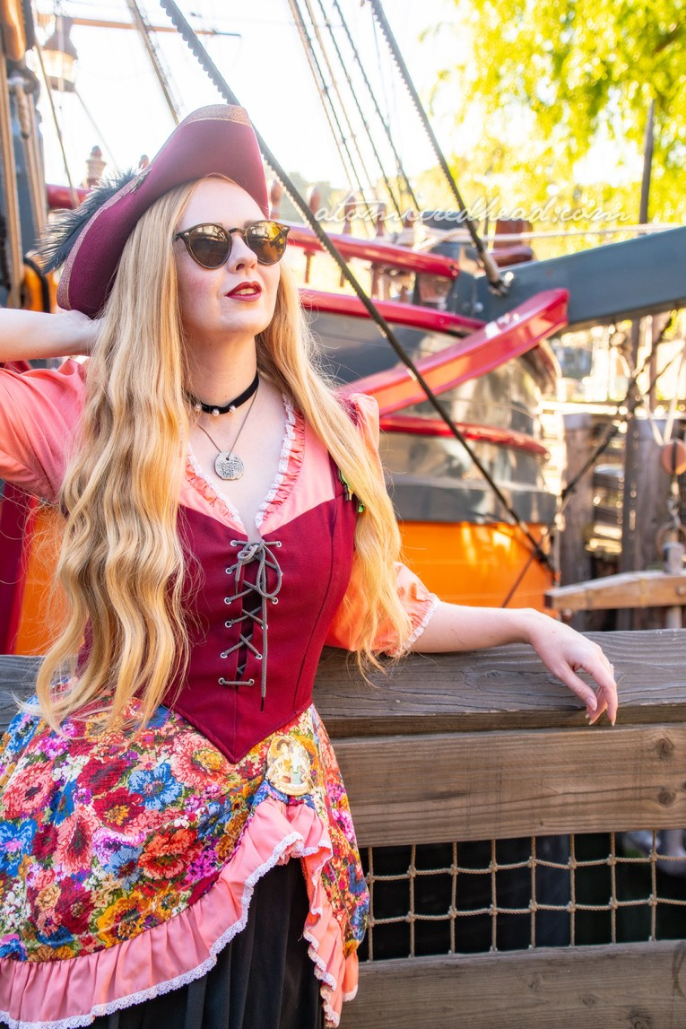 Myself, wearing a dress with peach sleeves, maroon corset, and floral skirt, worn over a black skirt to the knee, and a maroon pirate hat, standing in front of Disneyland's Sailing Ship Columbia.