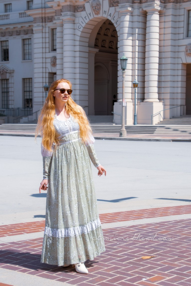 Me, standing in front of Pasadena City Hall, a tall, domed, Mediterranean style building, wearing a long pale green dress with small white flowers.