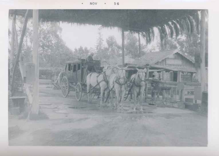 A black and white photo of the stage coach, which is pulled by four horses.
