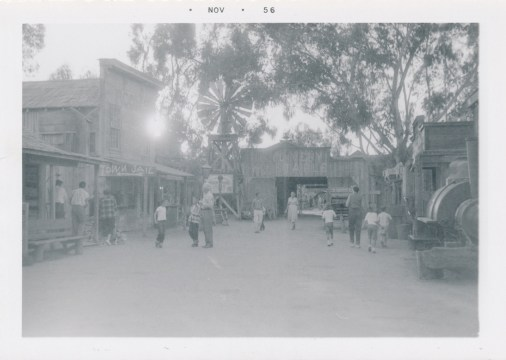 A black and white photo of Ghost Town, with Goldie's a two story hotel on the left, and at the end of the street a stable building.