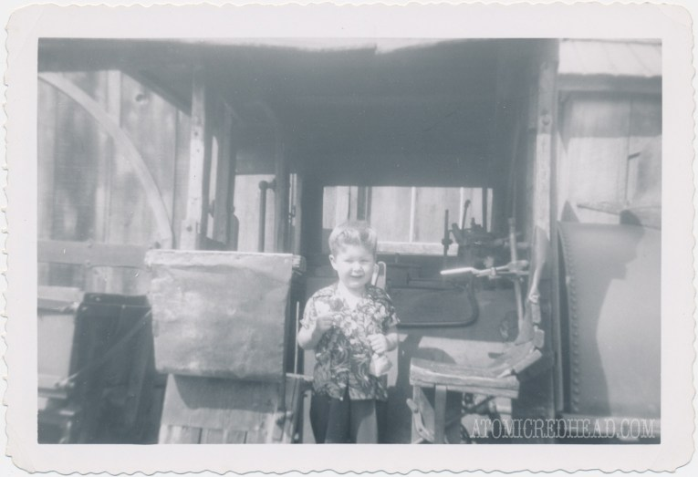 A black and white photo of my dad as a child in front of Old Betsy the borax train, holding rock candy.