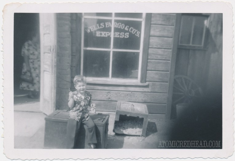 A black and white photo of my dad as a child in front of the general store, holding rock candy.