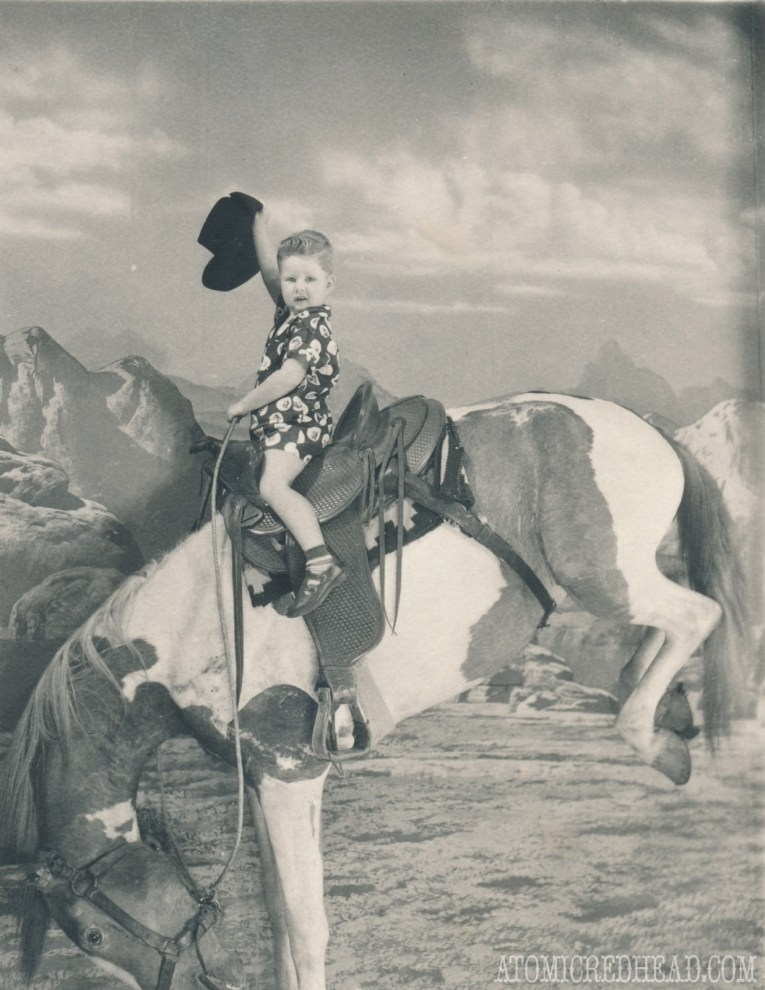 A black and white photo of my dad as a child on a taxidermied horse that is kicking.