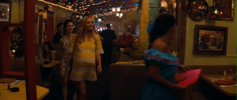 Margot Robbie, who plays Sharon Tate, wears a yellow mini dress, as she walks into El Coyote.