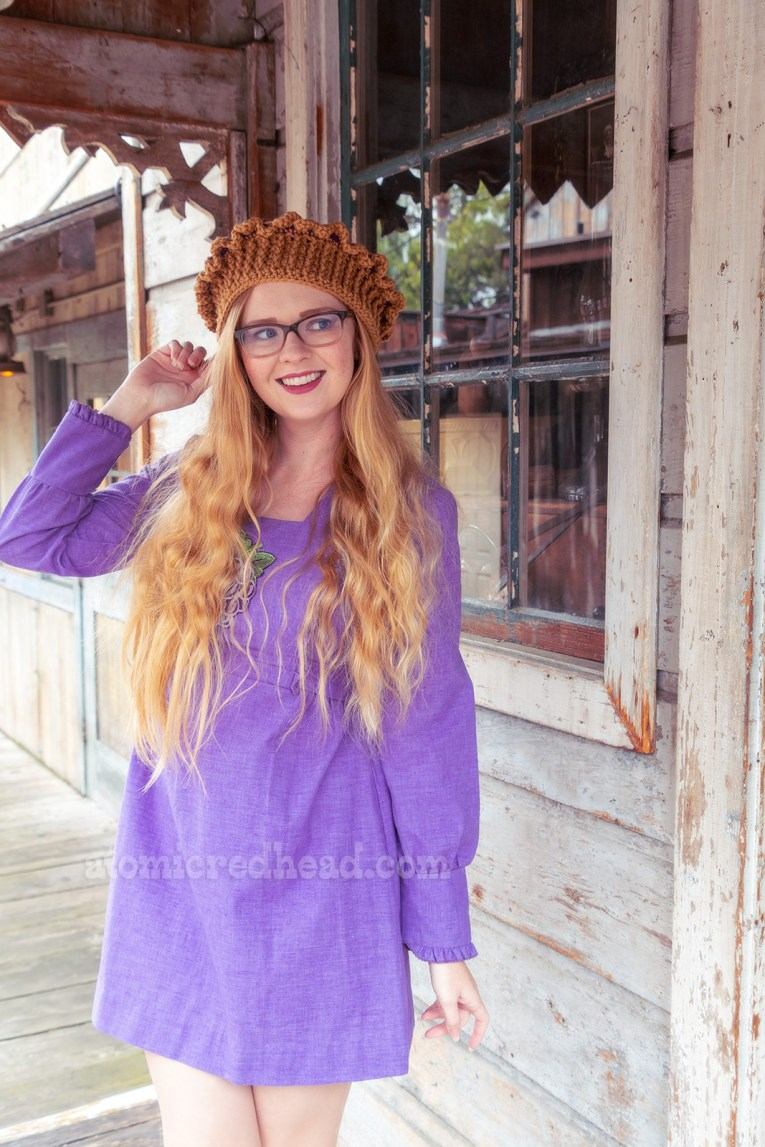 Myself standing on the porch of a small western style home, wearing a short, long sleeved purple dress with a large boysenberry embroidered on the front, and a boysenberry pie hat.