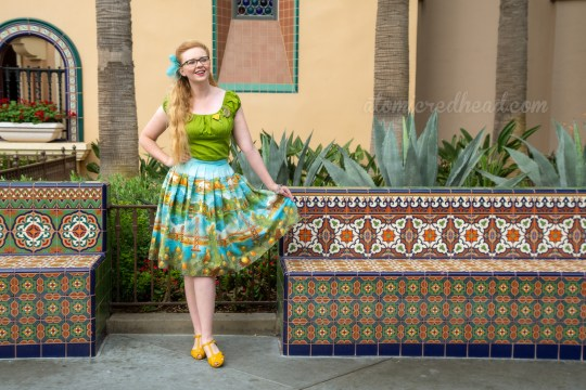 Myself standing in front of an adobe colored building and mosaic tile bench, wearing a green peasant top, with a D shaped brooch, and a poppy flower brooch, and a skirt featuring images of the Golden Gate Bridge, Catalina, and Mission Santa Barbara, a blue scarf is tied in my hair, and yellow shoes.
