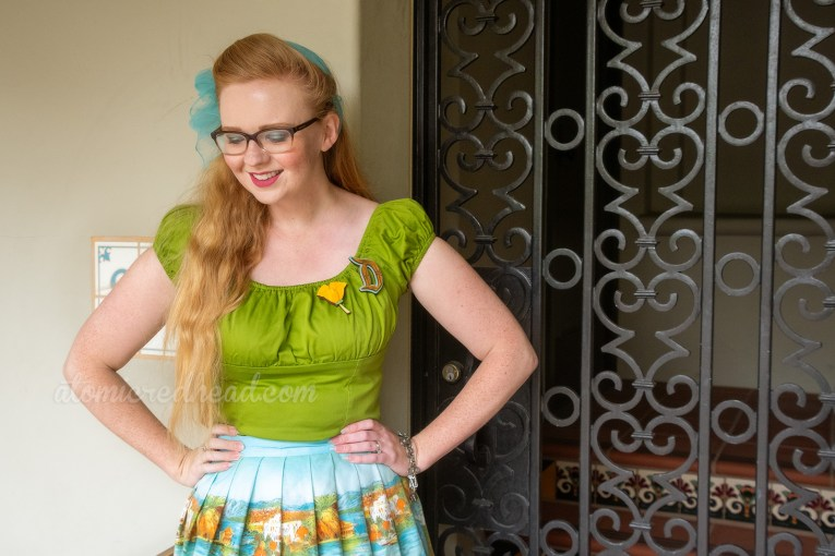 Myself standing in front of a wrought iron gate, wearing a green peasant top, with a D shaped brooch, and a poppy flower brooch, and a skirt featuring images of the San Fransisco-Oakland Bay Bridge, Catalina, and Mission Santa Barbara, a blue scarf is tied in my hair, and yellow shoes.