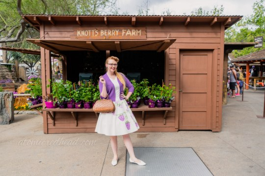 Myself, standing in front of a recreation of Knott's Berry Farm's first roadside stand, which sells boysenberry plants, wearing a purple sweater over a white dress with painted boysenberries.