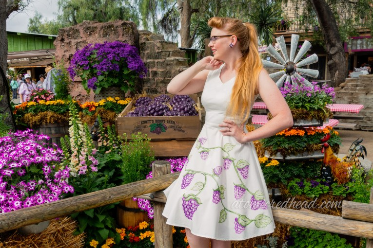 Myself, standing in front of a display of flowers, wearing a sleeveless white dress with painted boysenberries.