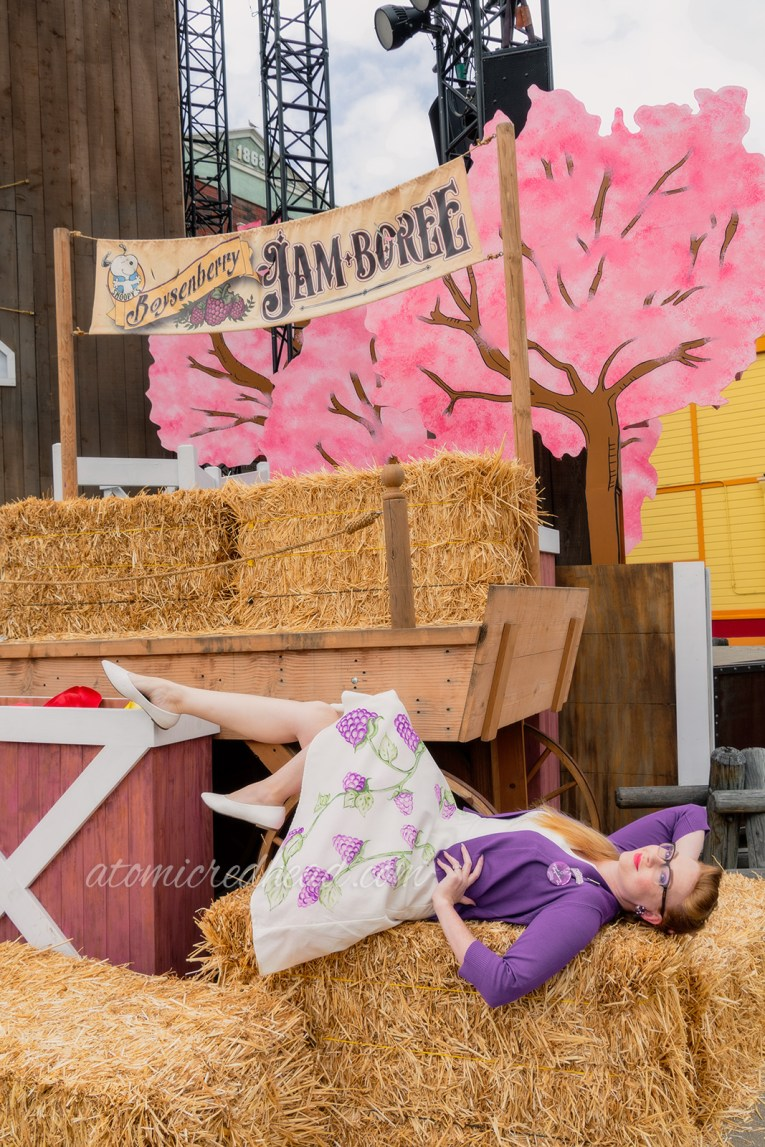 Myself laying on a bale of hay wearing my hand painted white dress and purple sweater.