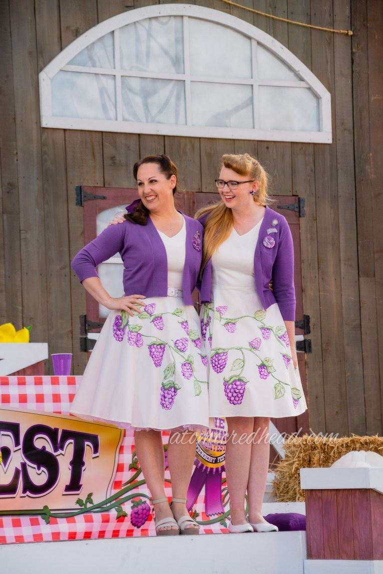 Kiley and I on stage during the contest, wearing the same thing, a purple sweater over a white dress with painted boysenberries.