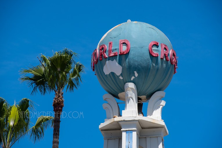 "Close-up of the globe, which features white continents, and red letters reading ""Crossroads of the World"""