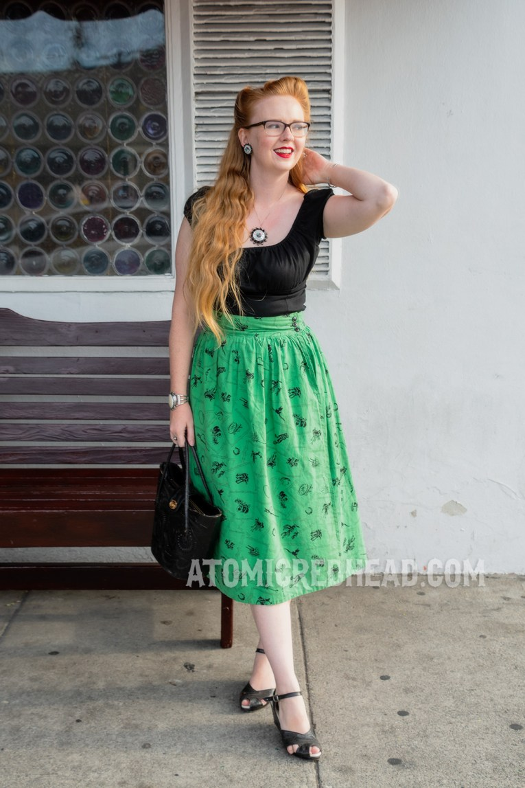 Myself wearing a black peasant style top, and a green skirt with a western print.