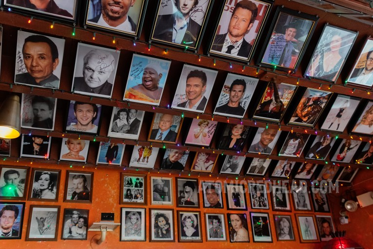 A wall covered with autographed photos of celebrities who have dined at El Coyote.