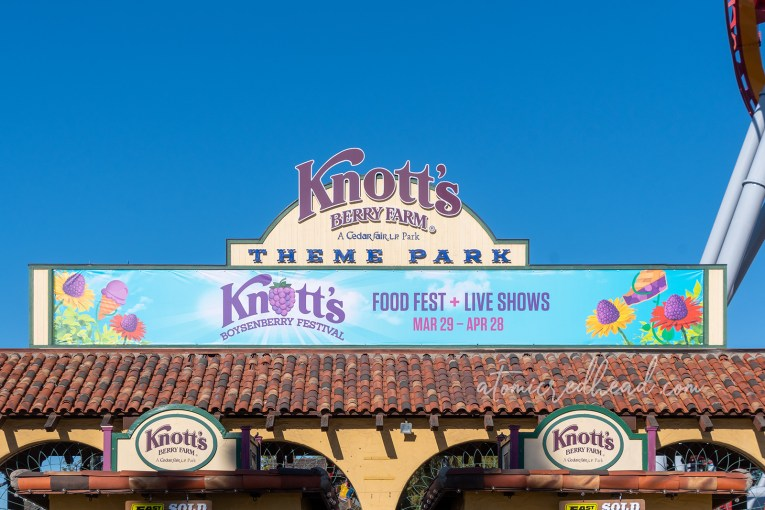 "Entrance to Knott's Berry Farm, which looks like old Spanish Colonial arches, and features a large sign reading ""Knott's Berry Farm"" and a banner reading ""Knott's Boysenberry Festival Food Fest + Live Shows"""