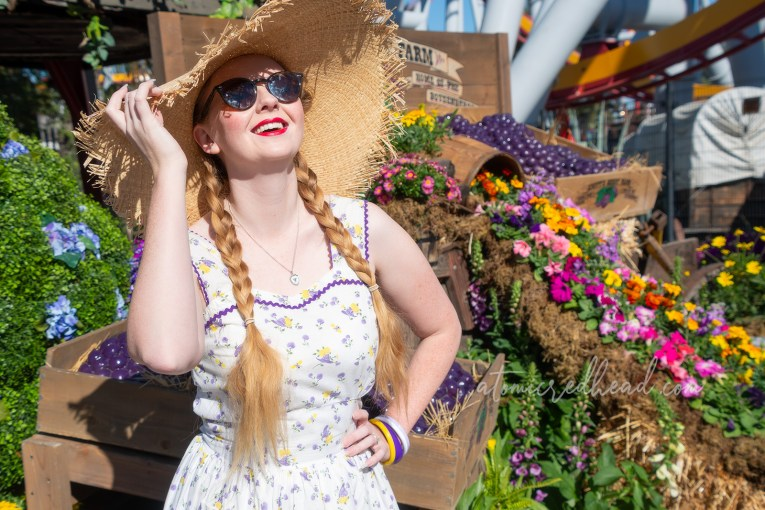Myself, standing next to a giant box of (fake) boysenberries, wearing a large straw hat and white dress with a yellow and purple floral and straw hat print.