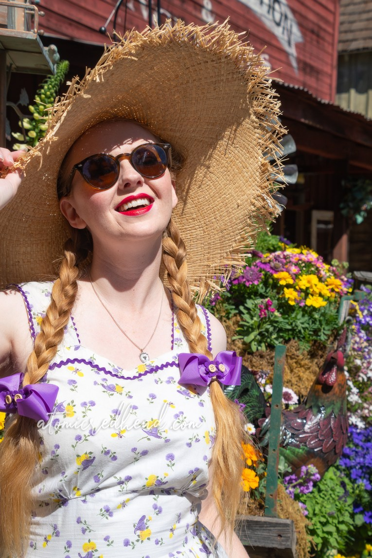Myself, standing next to a floral arrangement next to the Town Hall in Ghost Town, wearing a large straw hat and white dress with a yellow and purple floral and straw hat print.