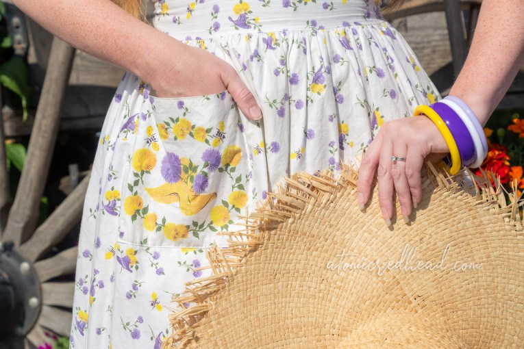 Close up of the pocket detail on my dress which features a straw hat and purple and yellow flowers.