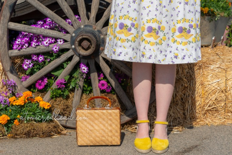 Close up of the hem of my skirt which features a straw hat and purple and yellow flowers. My shoes are also yellow.