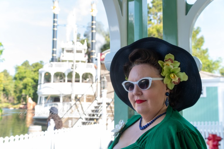 Dor, a brunette babe, wears an emerald green wiggle dress with a wide brimmed navy colored hat with lime green flowers, waits to board the Mark Twain which gleams in the sun behind her.