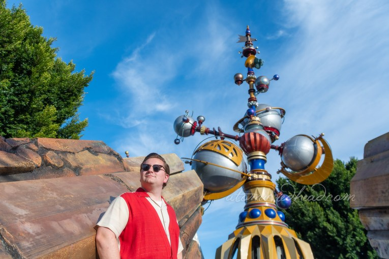 Patrick, wearing a red and white shirt and white pants leans against the golden rocks that flank the entrance to Tomorrowland, the gold and silver orbs of the Astro Obiter stand tall behind him.