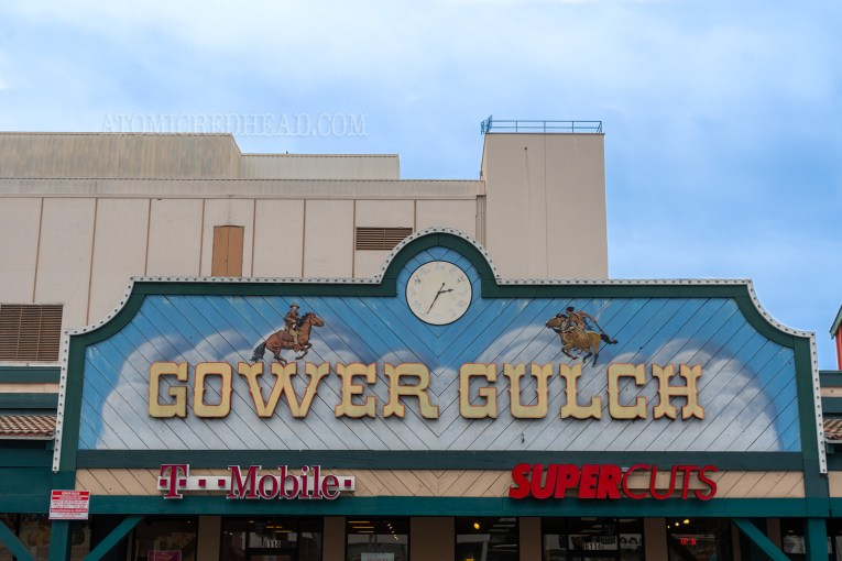 """A large sign above the stores reads """"Gower Gulch"""" in yellow western style letters. Above the letters are painted images of cowboys on horseback. A white clock face with various icons of the west serve as the numbers."""