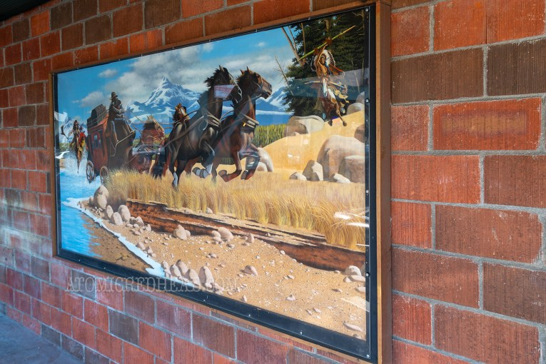 A mural of a horse drawn stage coach.