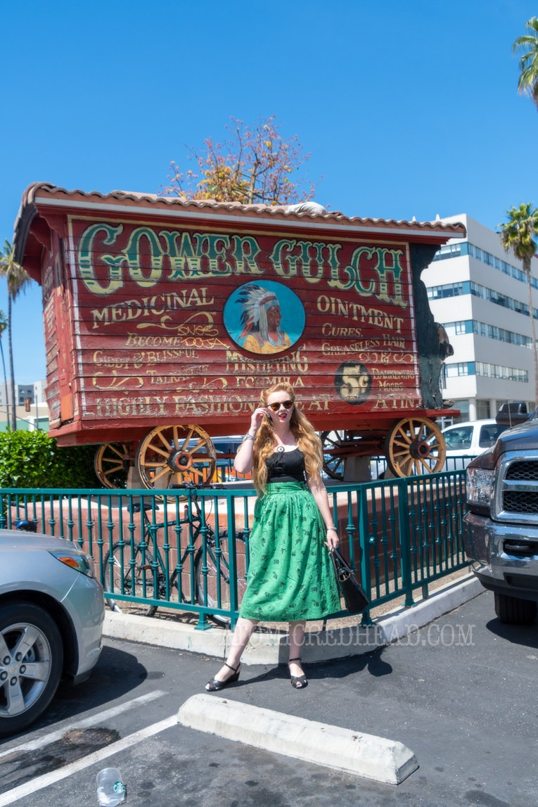 """Myself standing in front of the old west medicine wagon sits in the middle of the parking lot. It is red and reads """"Gower Gulch Medicinal Ointment"""" and has an image of an Indian wearing a headdress, wearing a black peasant top, and a green skirt with western images on it."""