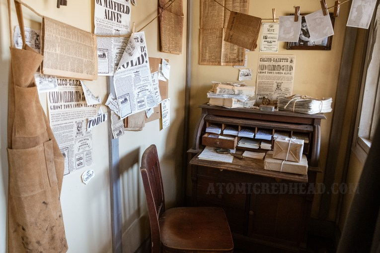 Interior of the Calico Gazette, which is covered with past issues of the newspaper, against the back wall a small dest sits, with papers and packages atop it.