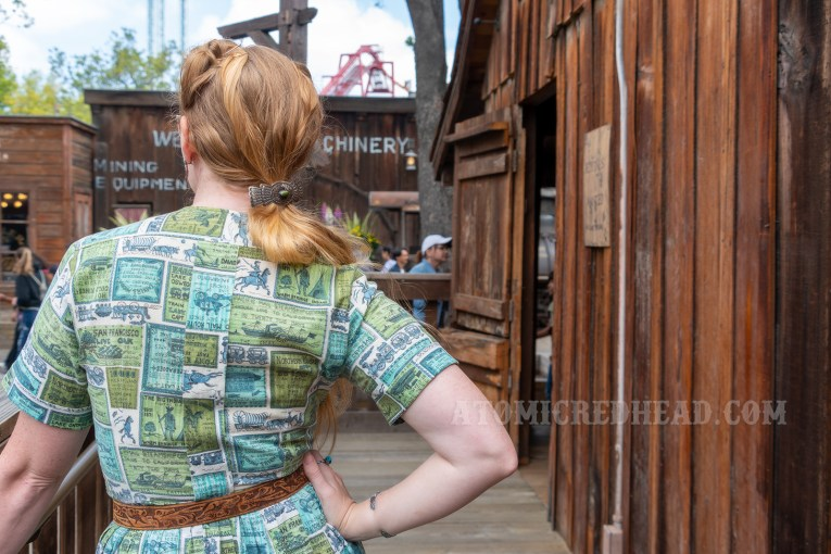 Myself standing against a worn wooden building, wearing a blue and green dress that features western images and faux adverts.