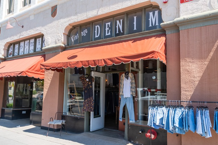 "A window reads ""Vintage denim"" above a burnt orange awning. A rack of denim shorts shits outside."
