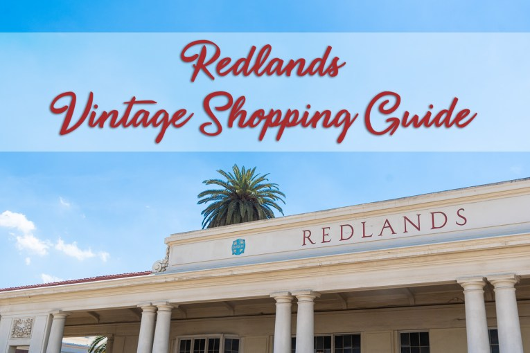 """A blue sky above the Redlands train station, which is a white building with pillars. """"Redlands"""" in red letters reads across the top of the building. An overlay in red type reads """"Redlands Vintage Shopping Guide"""""""