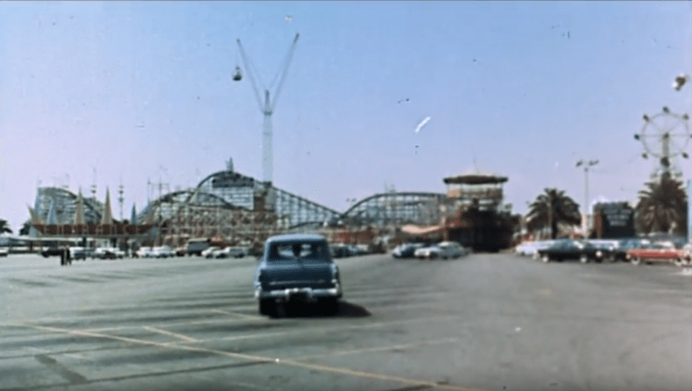 Screencap: A car drives through the parking lot of The Pike, with the tall Cyclone Racer in the background.