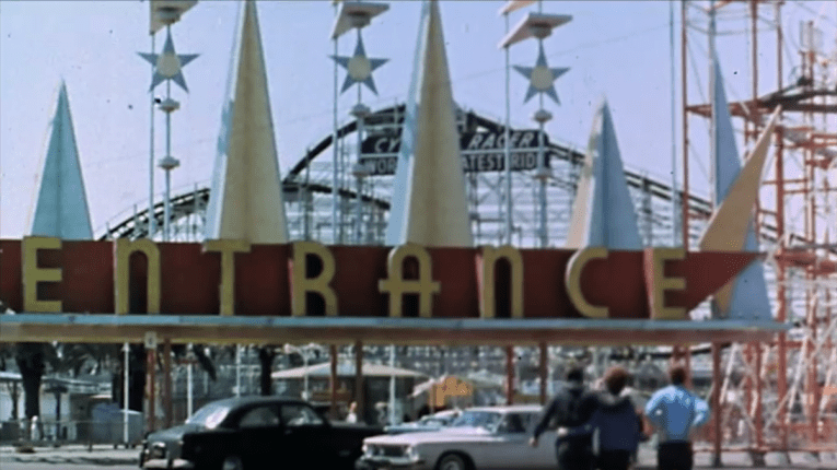 "Screencap: The entrance to The Pike, tall blue and yellow spires top the turnstiles, and yellow letters spelling ""Entrance"" above."