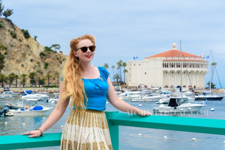 Myself standing on the beach with the Casino Building in the background. Wearing a bright blue peasant top, with a white and tan printed skirt.