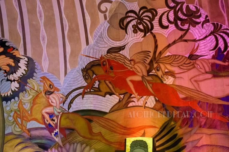 A close up of Native Americans atop horses painted near the theatre's stage.