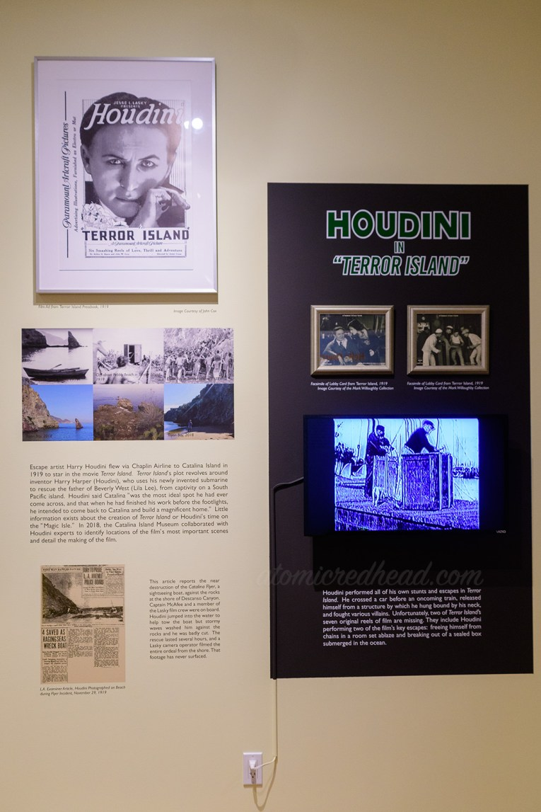 Wall dedicated to Houdini's time on the island, including black and white stills from the film, a poster from it, and a TV screen showing scenes from it.
