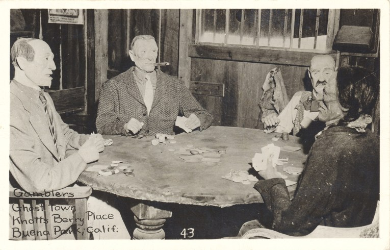 A black and white image of mannequins at a table playing cards.